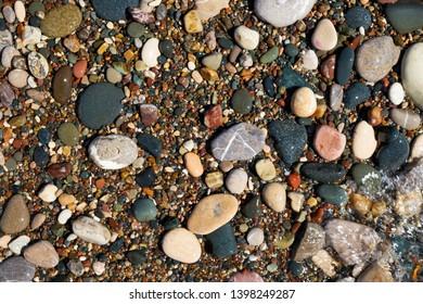 Wet pebble stones in water on Petra tou Romiou or Aphrodite Rock Beach, Cyprus. Stone natural background.