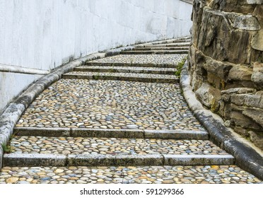 A wet pebbled staircase disappears around a corner.