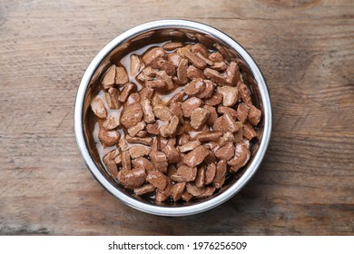 Wet pet food in feeding bowl on wooden table, top view - Shutterstock ID 1976256509