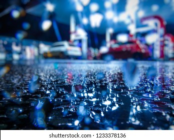 Wet petrol forecourt with out of focus cars and bokeh effect shot through the rain drops.