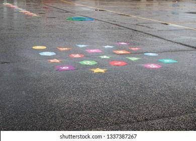 Wet playtime. Rainy day school playground games. Schoolyard abandoned after rain. Outdoor play area during indoor break.