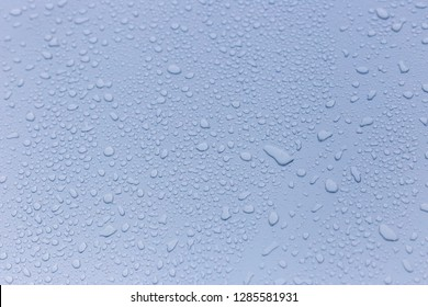 Wet rain drops on silver car hood. Abstract background. Water drops on red metal texture. Shallow focus, car body. Detail of red wet surface after rain