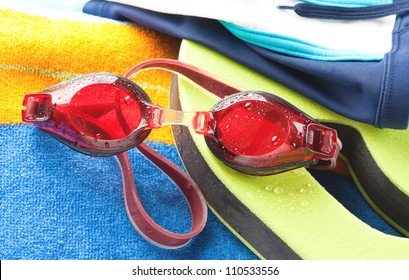 Wet red protective swimming goggles with a colourful beach towel and board in a watersports concept