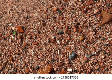 Wet Red Sand and Stones of the red Sea Coast. Natural Texture Background Terracotta Granite Pebbles, Schist and Sands