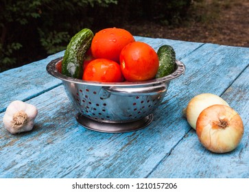 Wet red tomatoes and green cucumbers in the metal colander. Onion and garlic on the wooden table. Ripe summer vegetables. Vegetarian food. Preparing the salad. Close-up.