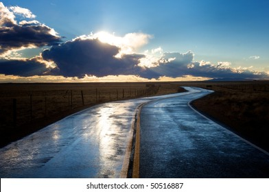 Wet road into sunset