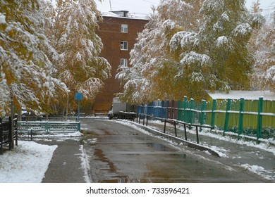 Wet road with puddles and snow, trees with yellow leaves, covered with snow, a house in a city yard. The first snow in the autumn, in October. Autumn and winter background