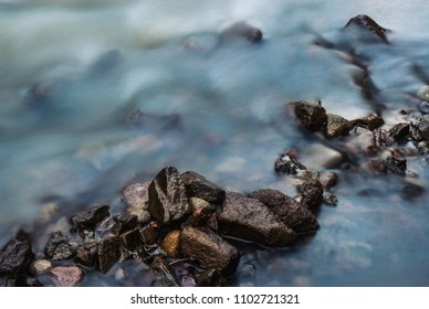 Wet rocks and pebbles close up in fast flow cold water mountain creek, long exposure image