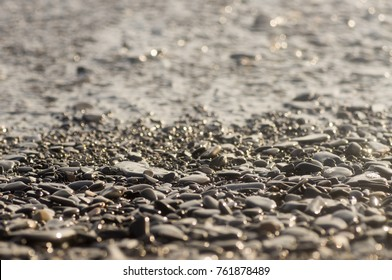 Wet rocky pebbly shore with a tidal wave in the setting sun close-up