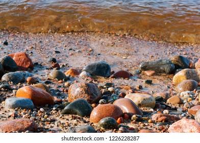 wet sea stones, coastal strip, wave rolls on the stones