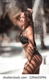 Wet sexy bikini model enjoying outdoor tropical shower at Maldives. Young woman showering outside by palms at summer vacation. Brunette girl in black swimwear enjoying natural water on exotic beach.