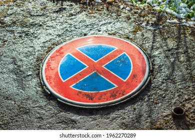 Wet shining red road sign as sewerage cover, red cross over blue metal circle. dirty, grime, water on top. Green moss on concrete, small rocks, puddle, rusted metal frame, sun, spring day