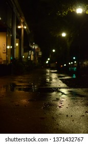Wet sidewalk and street at night after rain.