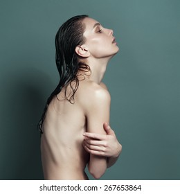 Wet skinny naked girl stands sideways visible ribs