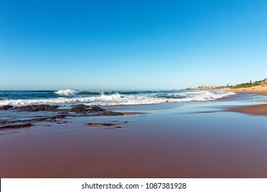Wet smooth shoreline beach sand with rocks ocean and waves against blue coastal skyline in Kwa-Zulu Natal, South Africa