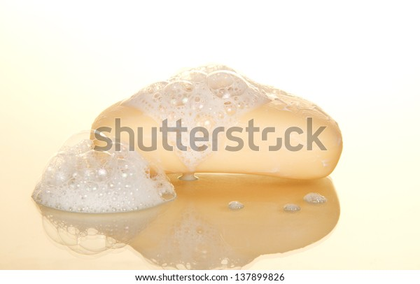 Wet soap with foam on a beige background