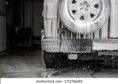 Wet and soapy black car at the car wash
