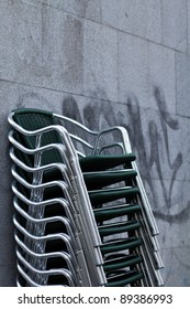 Wet stacked chairs next to a market in the center of Madrid