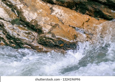 Wet stone by the river. Stormy blue river in the mountains. Background