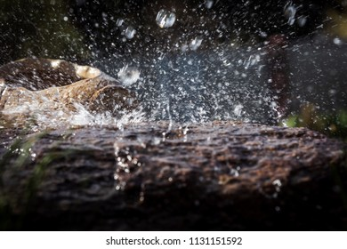 Wet stone and decorative antique urn in the rain. Rain water drop falling to the stone. Water is flowing and splashing around them.