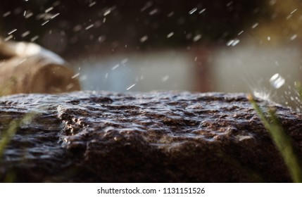 Wet stone in the rain. Rain water drop falling to the stone. Water is flowing and splashing around them.