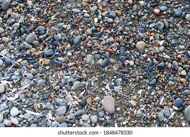 Wet stones and pebbles on sand
