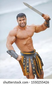 Wet strong man with a naked torso in historical armor holds a sword on the beach