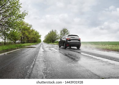 Wet suburban road with car on rainy day