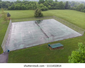 Wet tennis courts aerial view after rain showers in summer