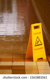 The wet tiles and clinker of a freshly wiped tunnel floor with a warning sign: Caution Slipping hazard!