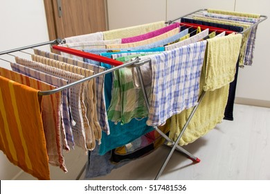 Wet towels hanging and drying on collapsible clotheshores lines indoors