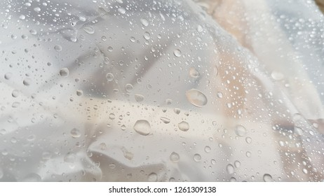 Wet transparent polyethylene film with droplets of water after rain. Water drops closeup. Wet smooth plastic surface texture. Rainy background. Grey tones backdrop. Rain weather abstract background