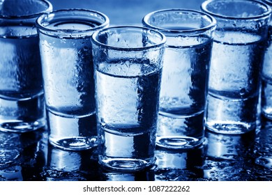 Wet transparent vodka shots. Weekend party background.