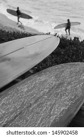 Wet and Waxed Surfboards With Surfers in Background