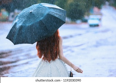 Wet weather. Autumn rain. Lonely girl in polka dots dress hold  black umbrella. Raining in city. Wet umbrella against the backdrop of the street. Woman was caught in the rain. Lonely unhappy girl