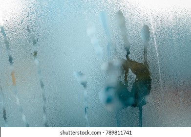 Wet window glass with hand shape print on natural abstract background. Close up picture textured foggy surface