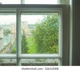 Wet window pane with rain water droplets and greenery background