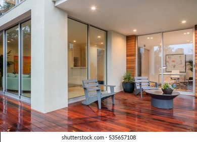 Wet wooden deck with furniture and open doors leading to inside.