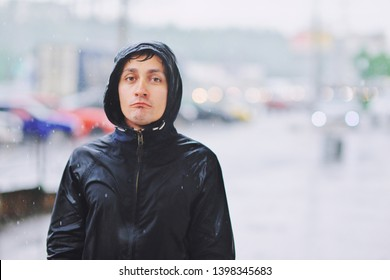 Wet young man in raincoat with unhappy face walks along the street during heavy rain, close-up. Autumn bad stormy weather concept. Sad person in wind jacket walking at rainy day storm
