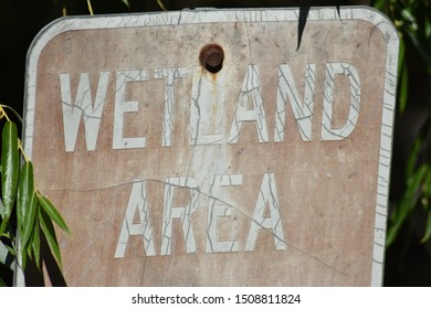 Wetland area sign worn out and old.