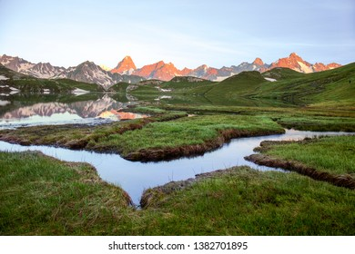Wetland with winding brooks at Lacs de Fenetre with reflection at sunrise and Grand Jorasses; Val Ferret; Mont Blanc; Col de Grand Saint Bernard at the mountain background, Switezrland