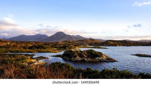 Wetlands and barrens on the coast, coastline and islands with mountains range in a distance, moody blue sky with clouds, Wiled Atlantic Way, Ireland