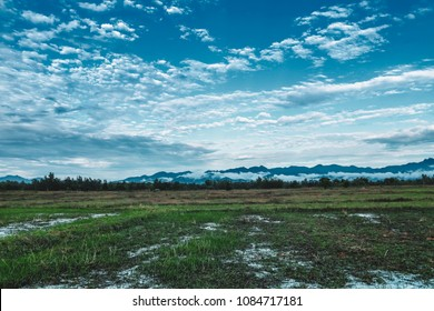 Wetlands in distant lands, scenic backdrop of sky and beautiful mountains.