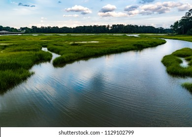 Wetlands river runs through reeds and into a coastal river underneath a dark and brooding sky