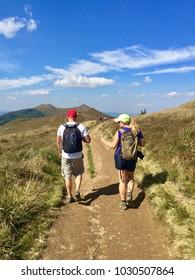 WETLINA, POLAND - SEPTEMBER 8, 2016: A couple hiking on a trail in Polonina Wetlinska, Bieszczady Mountains National Park in Poland on a sunny day.