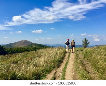 WETLINA, POLAND - SEPTEMBER 8, 2016: A couple hiking on a trail in Polonina Wetlinska, Bieszczady Mountains National Park in Poland on a sunny day with view to the mountain tops on the horizon.