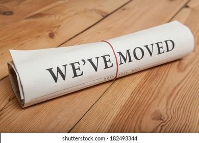 """we've moved"" newspaper on wooden floor"
