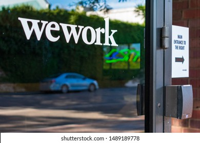 WeWork sign on the glass door leading to office shared coworking space building located in Silicon Valley - Palo Alto, California, USA - August 27, 2019