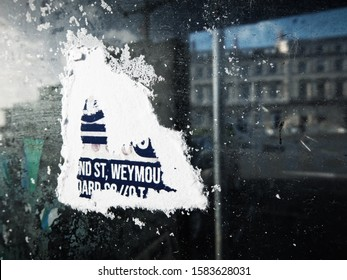 WEYMOUTH, DORSET, UK - December 9 2019: Close-up of a torn and weather-beaten poster stuck to the glass of a telephone box on the seafront esplanade, with blurred reflection of the buildings opposite.