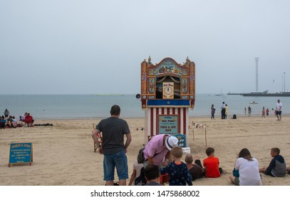 Weymouth Dorset United Kingdom 21 July 2019  -:  Holidaymakers waiting for  traditional Punch and Judy show booth on beach